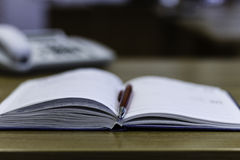 Caderno, pena e telefone na tabela Fotografia de Stock Royalty Free