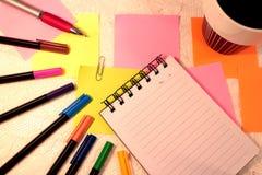 Caderno, penas de feltro em várias cores, notas pegajosas e uma xícara de café fotos de stock