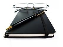Caderno preto com pena e vidros isolados no branco Imagens de Stock Royalty Free