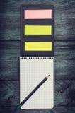 Caderno preto com uma folha em uma gaiola com lápis e notas pegajosas coloridas em um fundo rústico de madeira, vista superior Imagem de Stock