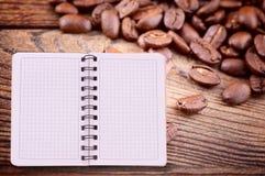 Caderno puro para o menu, registro da receita na opinião de tampo da mesa de madeira Feijões de café como o fundo Imagem de Stock