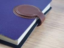 Caderno roxo do negócio com pele marrom para fechar-se no fundo de madeira Fotos de Stock