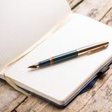 Caderno vazio aberto com a pena de fonte elegante Fotografia de Stock Royalty Free