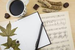 Caderno vazio aberto com xícara de café e livro da notação de música, no desktop de madeira Imagem de Stock