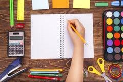 Caderno vazio aberto, mão com um quadro do brushwith do sup da escola imagens de stock