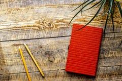Caderno vazio alaranjado com a flor na tabela de madeira do vintage Imagens de Stock