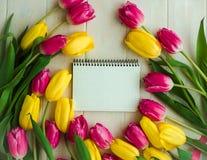 Caderno vazio com a flor cor-de-rosa e amarela, tulipas Fotos de Stock