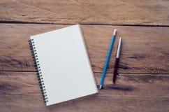 Caderno vazio com lápis e pena na tabela de madeira - ainda vida Fotografia de Stock