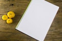 Caderno vazio com a laranja na tabela de madeira, caderno vazio com fotografia de stock royalty free
