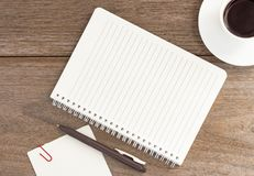 Caderno vazio com o copo de café no fundo de madeira Foto de Stock