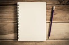 Caderno vazio com o lápis na tabela de madeira - ainda vida Fotografia de Stock