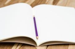 Caderno vazio com o lápis na tabela de madeira - ainda vida Fotografia de Stock Royalty Free