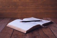 Caderno vazio com o lápis na tabela de madeira Foco seletivo Imagem de Stock