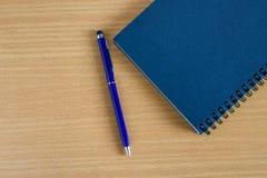 Caderno vazio com a pena na tabela de madeira Imagem de Stock