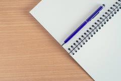 Caderno vazio com a pena na tabela de madeira Fotografia de Stock