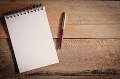 Caderno vazio com a pena na tabela de madeira - ainda vida Foto de Stock Royalty Free
