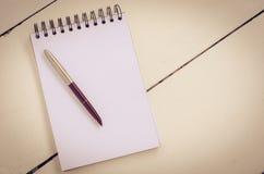 Caderno vazio com a pena na tabela de madeira - ainda vida Imagens de Stock