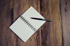 Caderno vazio com a pena na tabela de madeira - ainda vida Imagem de Stock Royalty Free
