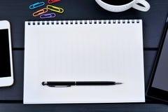 Caderno vazio com telefone e a tabuleta digital em uma tabela de madeira imagens de stock