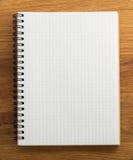 Caderno verificado na madeira fotos de stock