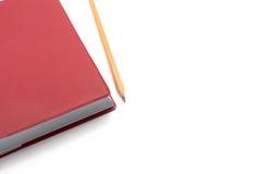 Caderno vermelho da tampa com o lápis de madeira no fundo branco Imagem de Stock
