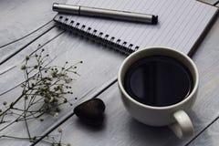 Caderno, xícara de café e chocolate dado forma coração Fotografia de Stock