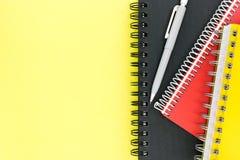 Cadernos amarelos, pretos e vermelhos com o lápis na tabela amarela Fotografia de Stock