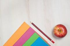 Cadernos da escola com lápis e maçã Fotografia de Stock