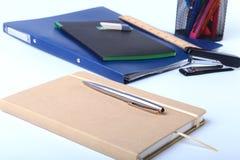 Cadernos e materiais de escritório coloridos na tabela branca Fotografia de Stock Royalty Free