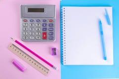 Cadernos e uma calculadora com artigos de papelaria diferentes em um fundo alaranjado e verde brilhante Fontes de escola fotos de stock