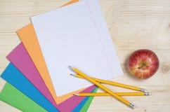 Cadernos, lápis e maçã da escola Fotografia de Stock