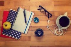 Cadernos, pena, vidros, maçã em um de madeira foto de stock royalty free
