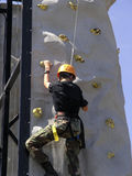 Cadet Climbing the Wall. A young cadet climbs a wall in a timed test of skill. Timed from ground to pressing a button at the top it encourages top physical royalty free stock photos