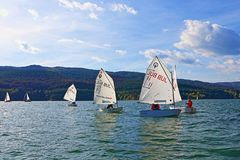 Kids racing sailing boats. Cadets racing in class Optimist regatta on Iskar Lake,Sofia Bulgaria. Picture taken on October 14th 2017 Royalty Free Stock Photo