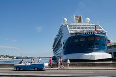 Cadillac, carro convertível clássico americano, na frente do forro do cruzeiro no porto de Havana, Cuba foto de stock royalty free