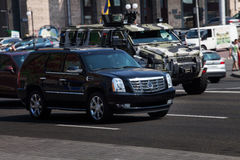 Cadillac Escalade rides around town. With armored personnel carriers Kraz. Military equipment travels through the city. BTR armored personnel carriers in a stock photography