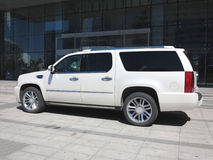 Cadillac Hybrid Suv,. A Cadillac hybrid with office building Royalty Free Stock Photos