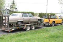 Cadillac sur un lit plat et remorqué par camion jaune Photographie stock