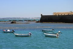 Boats off the coast of Cadiz near the fortress of Castillo Fortaleza de Santa Catalina. Stock Images