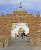 People passing the old entrance arch in Cadiz royalty free stock image