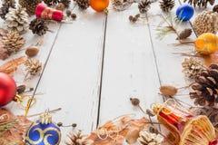 Cadre abstrait de Noël avec les cônes, l'écorce de pin, les glands, et les jouets Fond en bois blanc Images stock