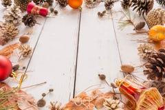 Cadre abstrait de Noël avec les cônes, l'écorce de pin, les glands, et les jouets Fond en bois blanc Photographie stock