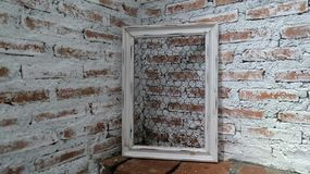 Cadre blanc sur le mur d'exposition de brique sous la lumière par le toit dans la chambre Photos stock