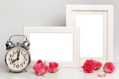 Cadre blanc vide, roses roses et réveil Voir les mes autres travaux dans le portfolio Images stock