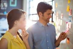 Cadre commercial et collègue regardant les notes collantes sur le tableau blanc Image libre de droits