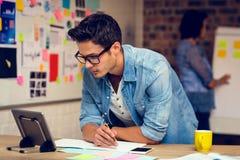 Cadre commercial regardant le comprimé numérique et prenant des notes en journal intime image stock