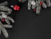 Cadre créatif de disposition fait de branches d'arbre de Noël, cônes de pin, cadeaux avec la décoration rouge sur le fond foncé image libre de droits