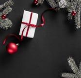 Cadre créatif de disposition fait de branches d'arbre de Noël, cônes de pin, cadeaux avec la décoration rouge sur le fond foncé images libres de droits