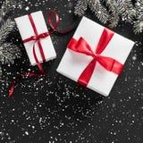 Cadre créatif de disposition fait de branches d'arbre de Noël, cônes de pin, cadeaux avec le ruban rouge sur le fond foncé E image stock