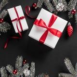 Cadre créatif de disposition fait de branches d'arbre de Noël, cônes de pin, cadeaux avec le ruban rouge sur le fond de papier fo photo stock